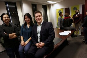 PHIL HOSSACK / WINNIPEG FREE PRESS - John Prystanski (right) poses with Duyen Chau and Jessie Asuncion (left) at a West land Foundation meeting Friday night. Other alumni and staff person chat in the background. December 21, 2018.